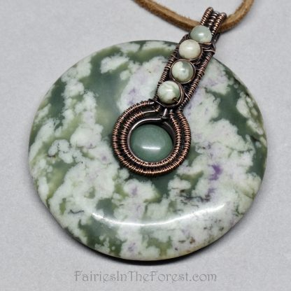 Copper wire wrapped Peace Jade donut pendant on a brown leather necklace.